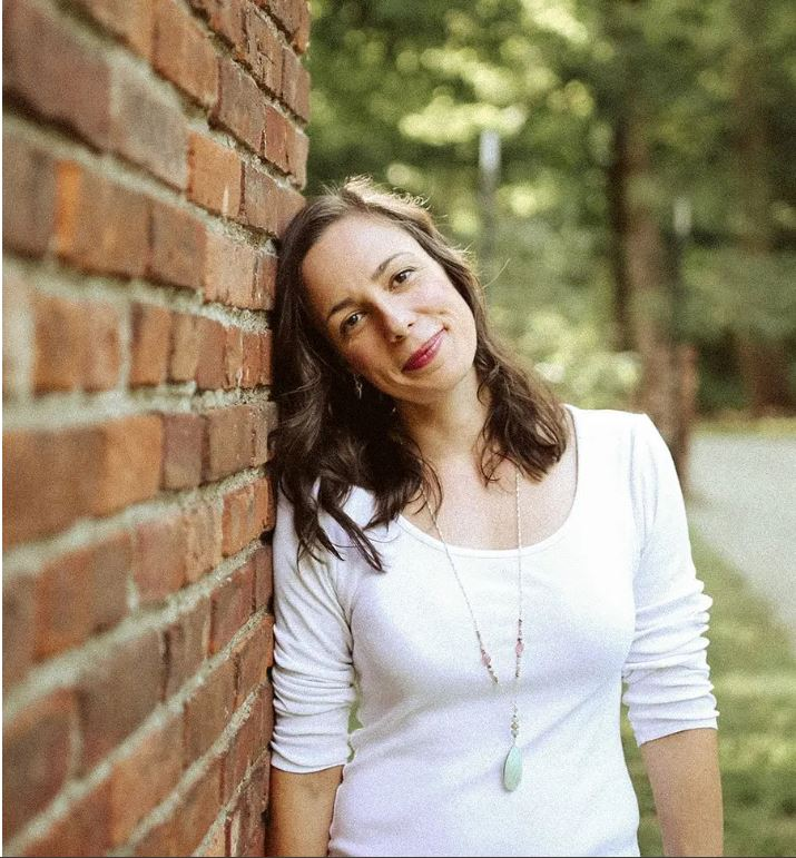 Melinda, a white woman, leans against a brick wall. Her hair is down and she is smiling.
